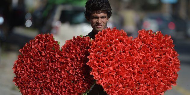 A Pakistani vendor carries heart-shaped bouquets for sale ahead of Valentine's Day along a street in...