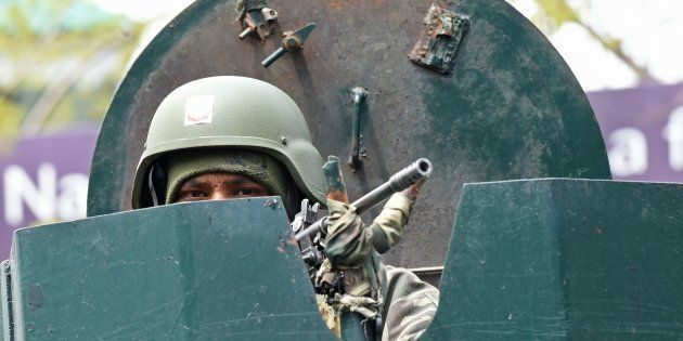 An Indian Border Security Force (BSF) soldier stands guard on top of an armoured vehicle outside a polling...