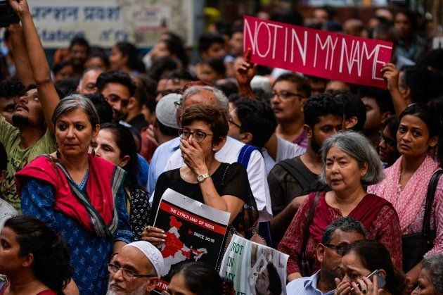 Protesters hold placards as they gather for a 'Not in my name' silent protest at Jantar Mantar in New...
