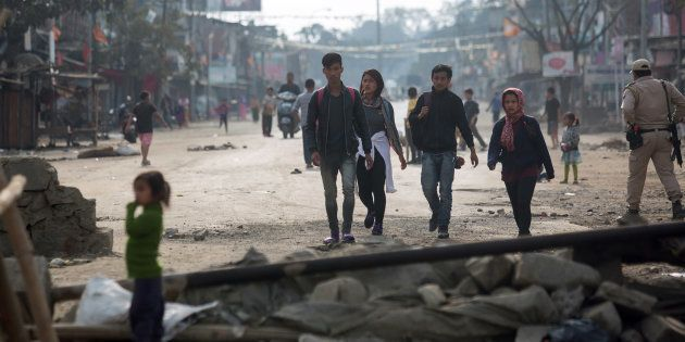 Pedestrians walk past temporary roadblocks on the outskirts of Imphal on December 20, 2016, during an...
