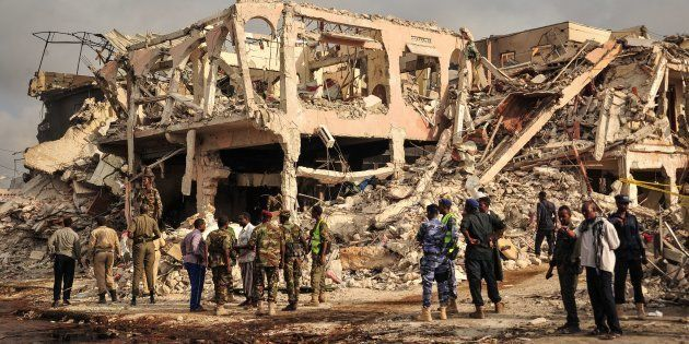 EDITORS NOTE: Graphic content/Somali security officers patrol on the scene of the explosion of a truck...