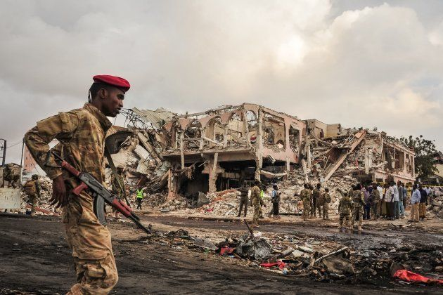 EDITORS NOTE: Graphic content / Somali soldiers patrol on the scene of the explosion of a truck bomb...
