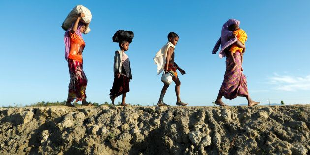 Rohingya refugees arrive at a beach after crossing from Myanmar, in Teknaf, Bangladesh October 15, 2017....