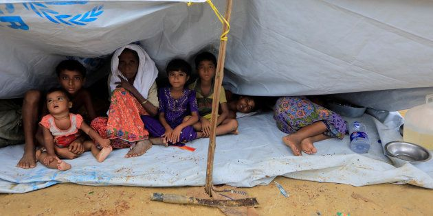 Rohingya refugees who crossed the border from Myanmar this week sit outside a school used as a shelter...