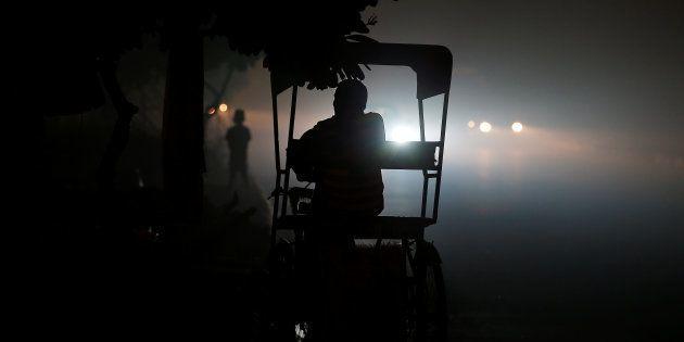 A rickshaw puller waits for customers along a roadside amidst heavy smog in New Delhi, India November...