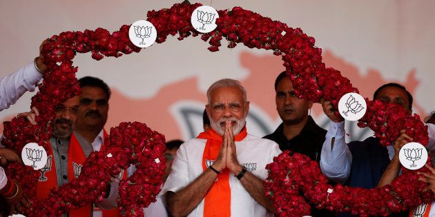 India's Prime Minister Narendra Modi is garlanded by supporters during a public rally at Bhaat village...