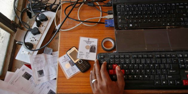 An operator works on his table while enrolling villagers for the Unique Identification (UID) database...