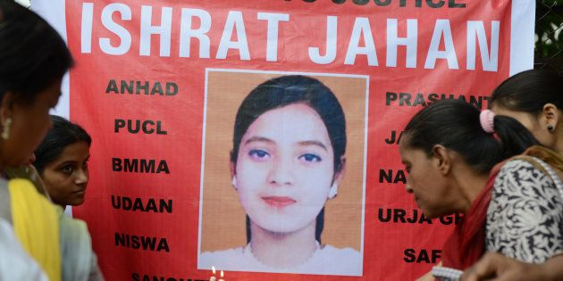 Supporters hold candles in front of a banner bearing the portrait of Ishrat Jahan during a protest in...