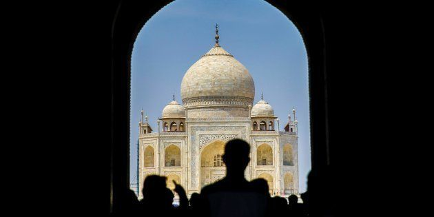 Tourists are seen as renovation process continue at Taj Mahal, one of the wonders of the world, in Agra,...