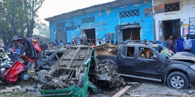 People stand among damages at the scene of a blast after two car bombs exploded in Mogadishu on October...