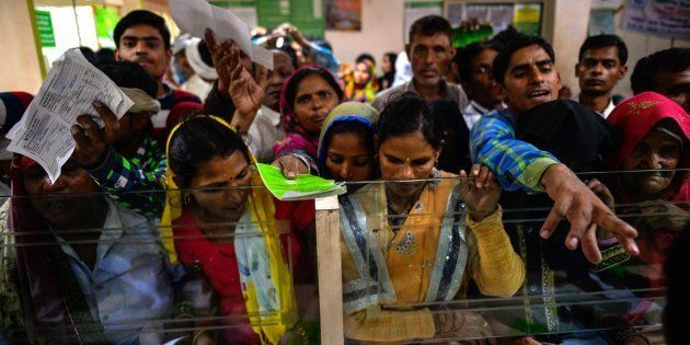 In this photograph taken on November 16, 2016, Indian villagers wait inside the bank to make the transactions...