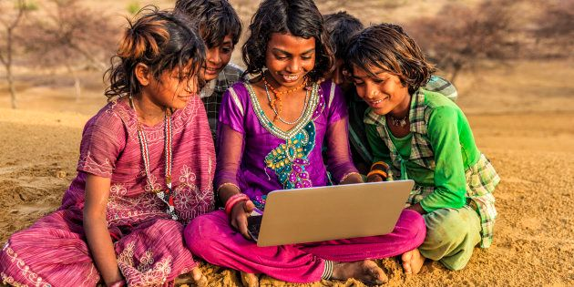 Happy Indian children, sitting on a sand dune and using laptop in desert village, Thar Desert, Rajasthan,