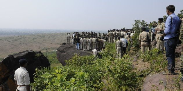 Policemen surround the area where eight SIMI terrorists were killed in an encounter lying on ground at...