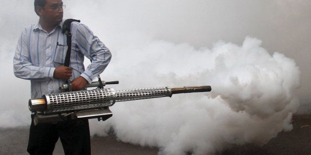A health worker fumigates a residential area to prevent the spread of dengue fever in Chandigarh, India,...