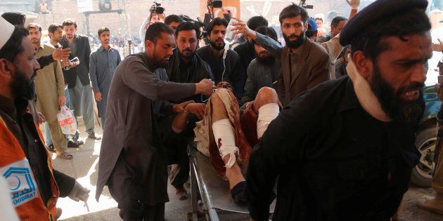 Hospital workers transport a man injured in the Charsadda blast to the hospital in Peshawar, Pakistan...