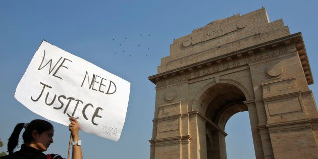 A demonstrator holds a placard in front of the India