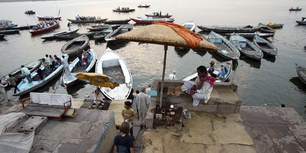 FILE PHOTO: Tourists board a boat, as a Hindu priest looks on, at the Dashashumedh ghat on the banks...