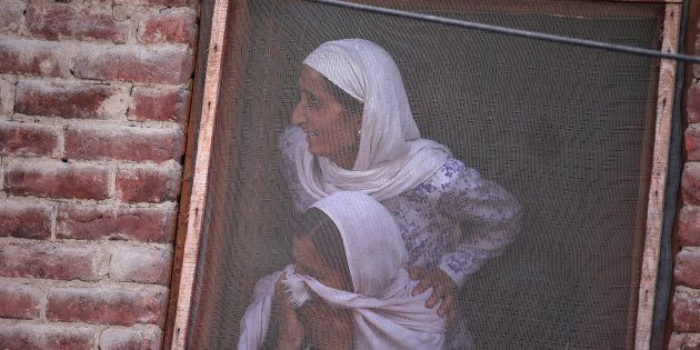 Kashmiri women watch the funeral of Muzaffar Ahmad Pandit, a civilian, who according to local media succumbed...