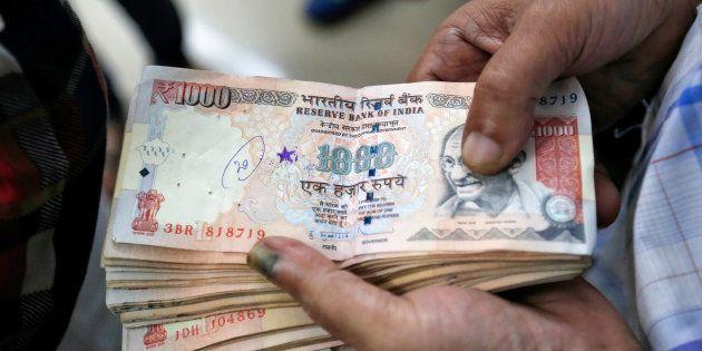 A customer waits to deposit 1000 Indian rupee banknotes in a cash deposit machine at bank in Mumbai,...