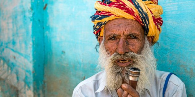 Senior indian man with vibrant colorful turban holding his tobacco pipe in front of blue wall in the streets of Rajasthan.