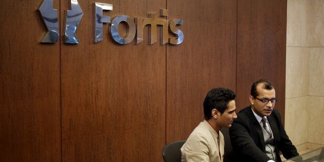 Employees sit on the helpdesk reception of the Fortis Memorial Hospital at