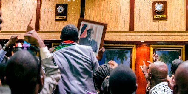 People remove, from the wall at the International Conference centre, where parliament had their sitting,...