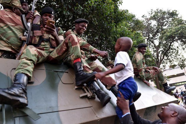 People celebrate with Zimbabwe Defence Force soldiers in the streets of Harare, after the resignation...