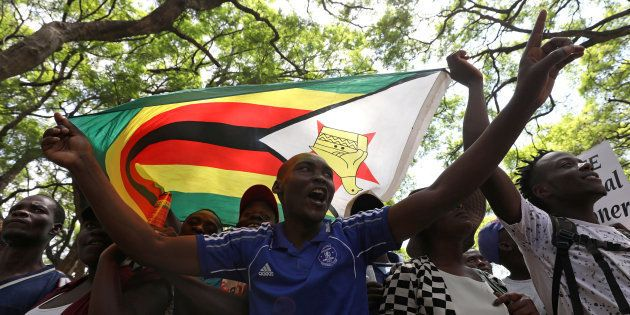 Protesters call for Zimbabwean President Robert Mugabe to resign across the road from parliament in Harare,...