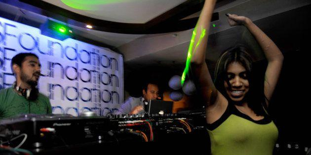 A woman dances as Indian disc-jockeys Nasha (C) and Nucleya (L) play music at a nightclub in New