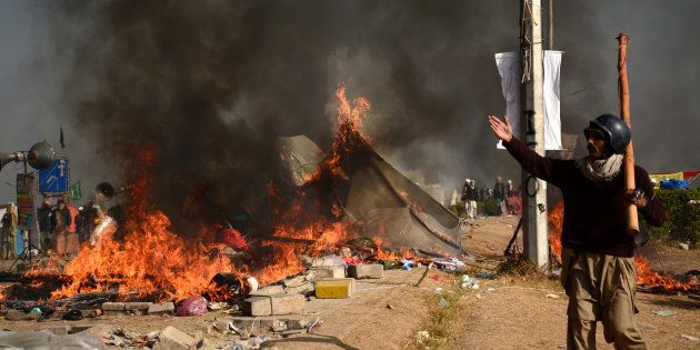 A protester walks near burning tents during clashes with police at Faizabad junction in Islamabad, Pakistan...