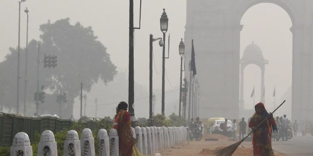 A sweeper cleans a road amid heavy smog near India Gate in New Delhi on November 16,