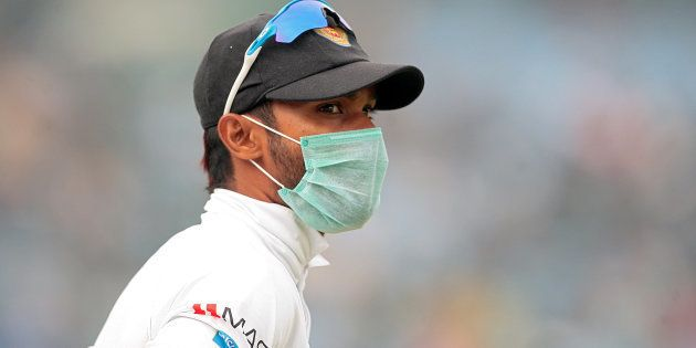 A Sri Lankan player, wearing a face mask, stands in the field.