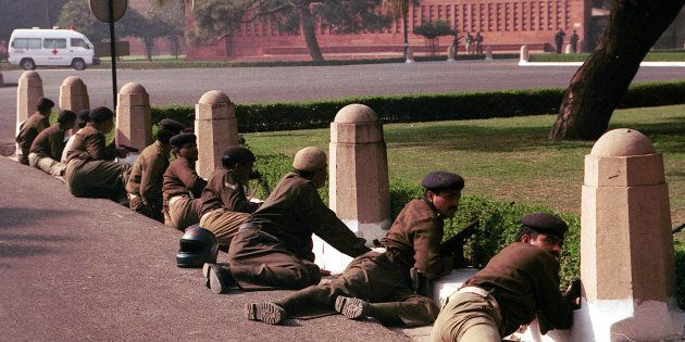 Delhi police commandos take cover outside the Indian parliament buildings December 13, 2001 in New Delhi, India.