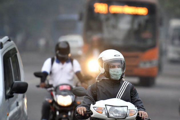 A motorcyclist wears a surgical mask on the streets of New Delhi.