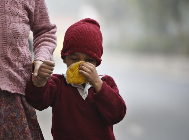 A child taking precautions against cold weather and smog at Green Park, on December 4, 2017 in New Delhi,