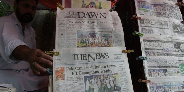 A Pakistani vendor arranges morning newspapers featuring front page coverage of Pakistan's victory against...