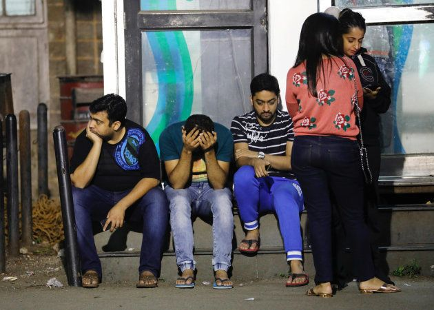 Friends of a victim killed in a fire at a restaurant wait at a hospital in Mumbai, India, December 28,