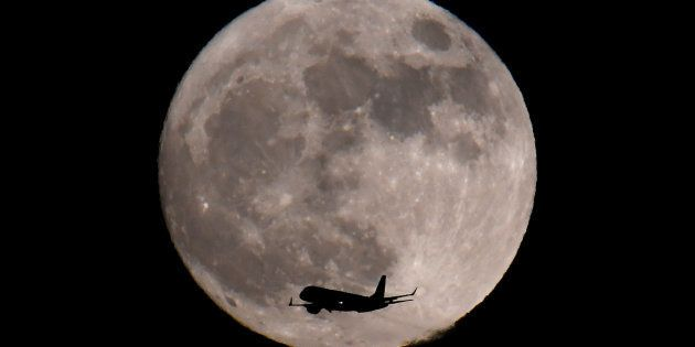 A passenger plane, with a 'supermoon' full moon seen behind, makes its final landing approach towards...