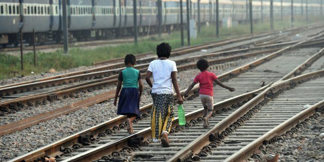 Indian children walk along the railway tracks after defecating in the open on International Toilet