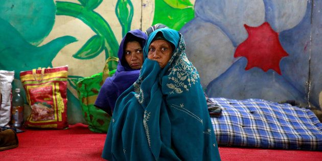 Women wrap themselves in blankets in a government shelter for homeless people to escape the cold in Delhi,...