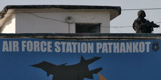An Indian security personnel stands guard on a building at the Indian Air Force (IAF) base at Pathankot...