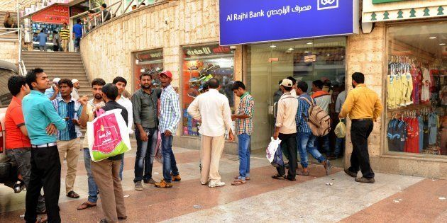 Indian workers queue outside a bank branch in the Saudi Arabian port city of Jeddah on August 4,