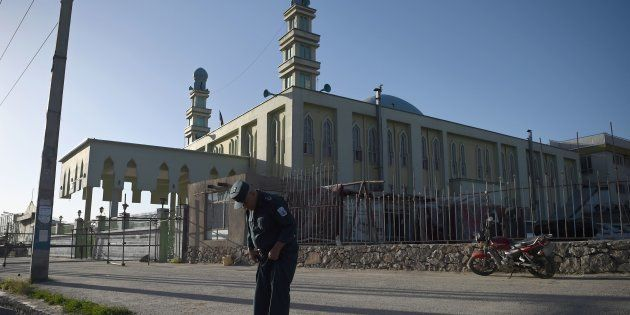 An Afghan security personnel looks at the ground in front of the Al-Zahra mosque in Kabul on June 16,...