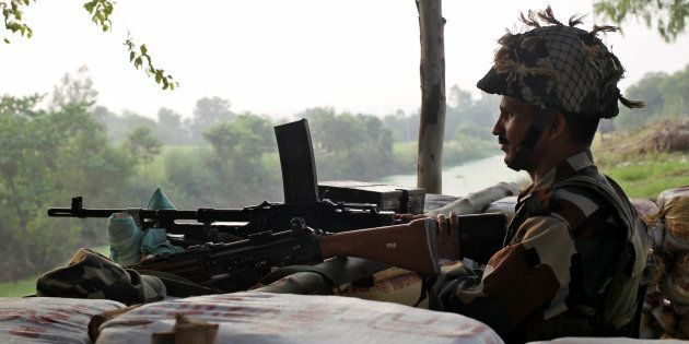 An Indian army soldier keeps guard from a bunker near the border with Pakistan in Abdullian, southwest...