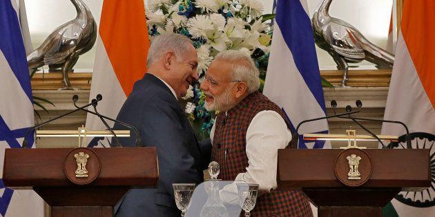 Israeli Prime Minister Benjamin Netanyahu and his Indian counterpart Narendra Modi hug after attending...