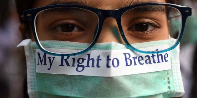 TOPSHOT - An Indian youth wearing a pollution mask participates in a march to raise awareness of air...