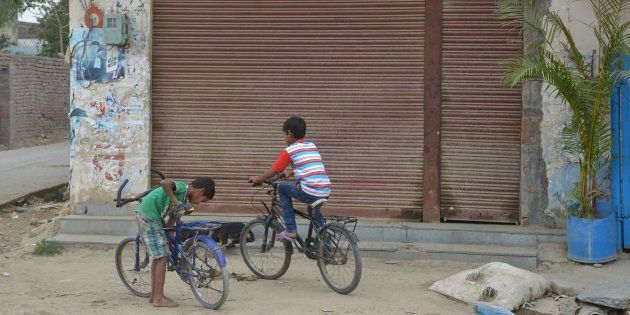 This picture shows children cycling in front of a closed liquor shop near a national highway on the outskirts...