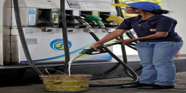 A worker fills a bucket with diesel at a gas station in the eastern Indian city of