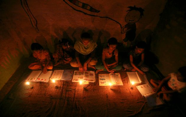 Muslim girls study in the light of candles inside a madrasa or religious school during power-cut in Noida...