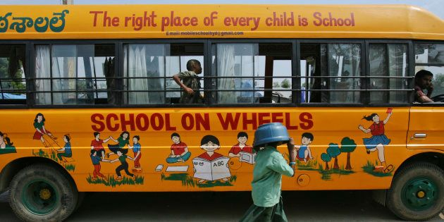 Bhavani, 8, covers her head with a plastic container as she walks past a bus which has been converted...